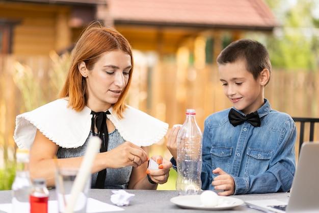 Mutter und sohn machen zu hause physikalische experimente. eine erfahrung mit einem kind, wie man mit feuer ein gekochtes ei in den schmalen hals einer plastikflasche legt. hausgemachte kreativität mit einem kind