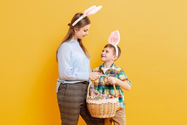 Mutter und sohn mit korb mit bemalten eiern