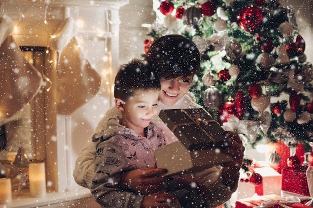 Mutter und sohn öffnen ein weihnachtsgeschenk in einer box