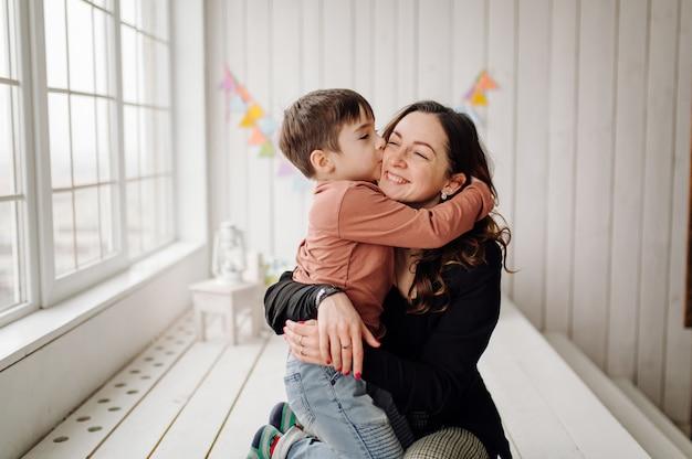 Mutter und sohn posieren im studio und tragen freizeitkleidung