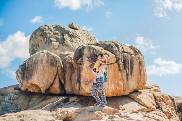 Mutter und sohn reisende am hon chong kap, gartenstein, beliebte touristenziele in nha trang. vietnam