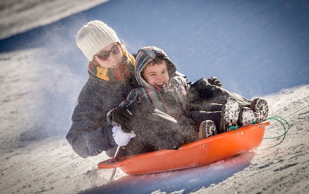 Mutter und sohn rodeln im schnee