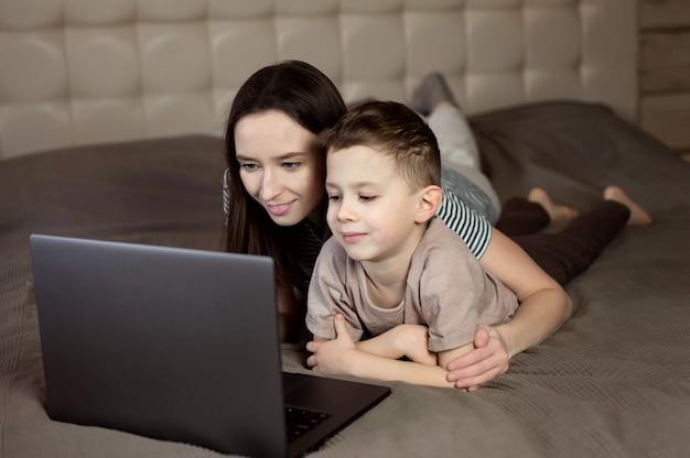 Mutter und sohn schauen auf den computerbildschirm