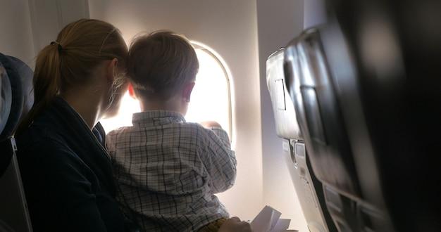 Mutter und sohn schauen im flugzeug auf den strahler