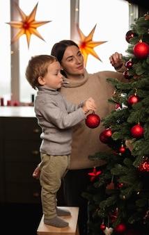 Mutter und sohn schmücken den weihnachtsbaum