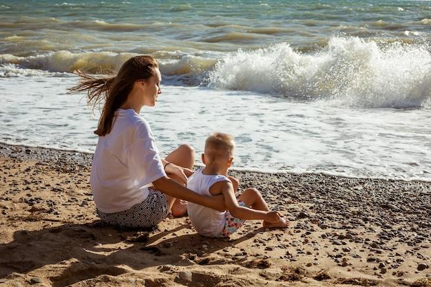 Mutter und sohn sitzen am meer an einem sonnigen sommertag, urlaubskonzept