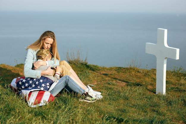 Mutter und sohn sitzen auf dem grab eines soldaten. mama brachte ihren sohn am gedenktag 27. mai zum grab seines vaters