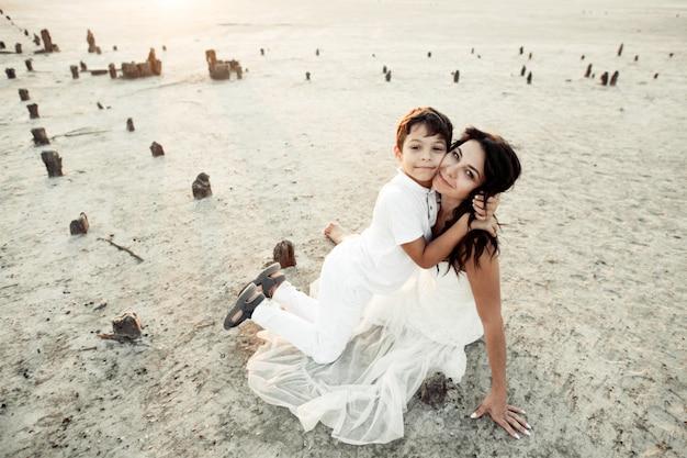 Mutter und sohn sitzen in weißen kleidern im sand, lächeln und umarmen sich