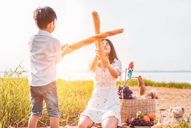 Mutter und sohn spielen fechten mit brot zusammen beim picknick im freien in der nähe von see oder fluss