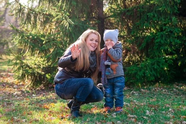 Mutter und sohn spielen im herbstpark