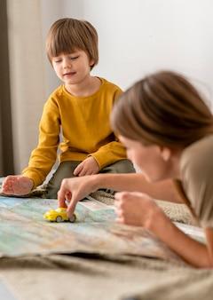 Mutter und sohn spielen zusammen mit autofigur und karte