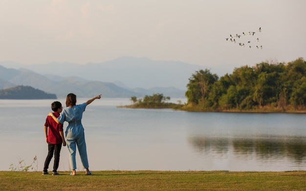 Mutter und sohn stehen neben großem see und sehen bergblick im hintergrund, mutter zeigt finger auf vögel, die im himmel fliegen. idee für familientouristen reisen zusammen.