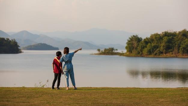 Mutter und sohn stehen neben großem see und sehen bergblick im hintergrund, mutter zeigt finger auf wald. idee für familientouristen reist gemeinsam zum outdoor-trip.
