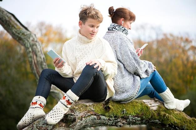 Mutter und sohn teen sitzen mit dem rücken zusammen auf einem ast und benutzen handys und headsets