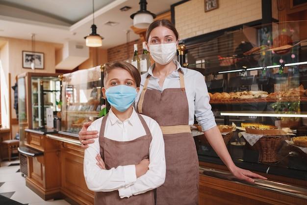Mutter und sohn tragen medizinische gesichtsmasken und arbeiten in ihrer familienbäckerei