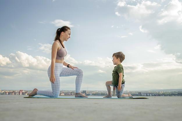 Mutter und sohn trainieren auf dem balkon