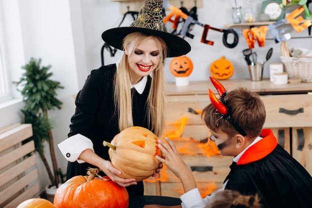 Mutter und sohn überlegen sich kürbis und haben lustige stunden zu hause. halloween