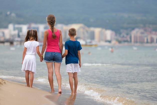 Mutter und sohn und tochter mit zwei kindern, die zusammen auf sandstrand im meerwasser im sommer mit bloßen füßen in den warmen meereswogen gehen.