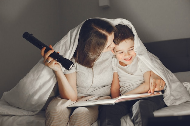 Mutter und sohn unter der decke im bett lesen ein buch.