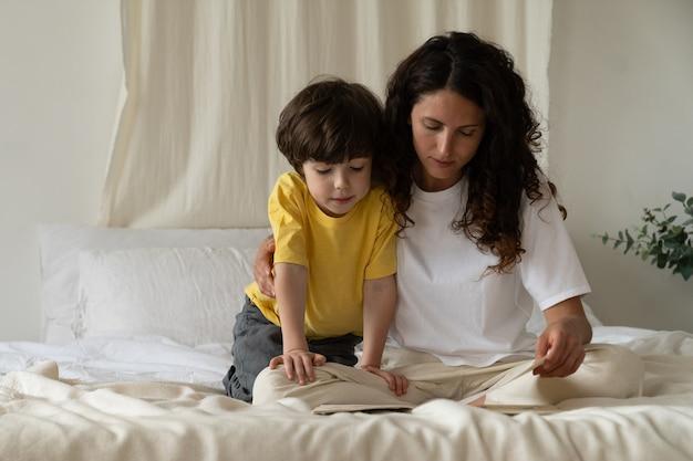 Mutter und sohn verbringen morgens zeit im schlafzimmer, sitzen auf dem bett und lesen zusammen ein interessantes buch