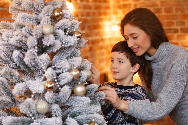 Mutter und sohn zu hause schmücken einen weihnachtsbaum.