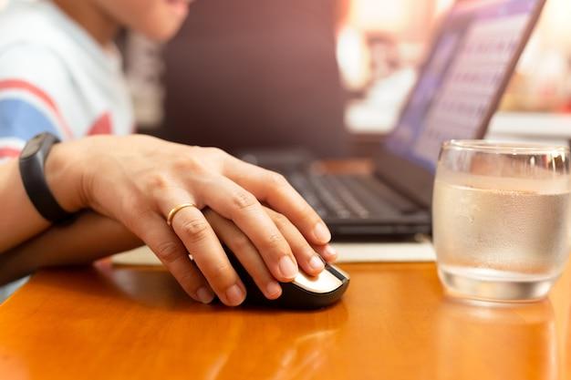 Mutter- und sohnhand, welche die laptop-computer maus zu hause arbeitet hält