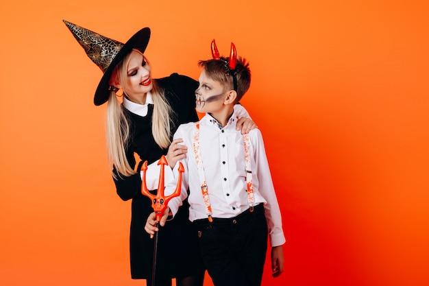 Mutter und sonne im teufelmaskerademake-up, das sich schaut. halloween