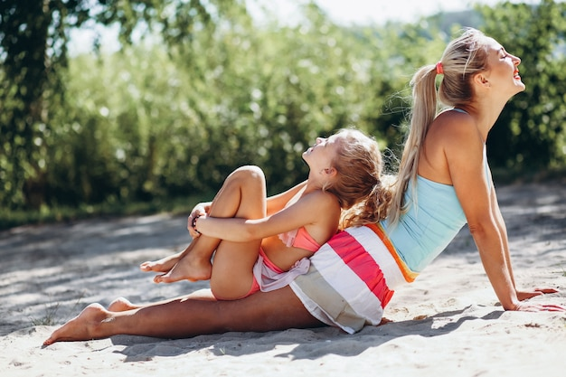 Mutter und tochter am übenden yoga des strandes