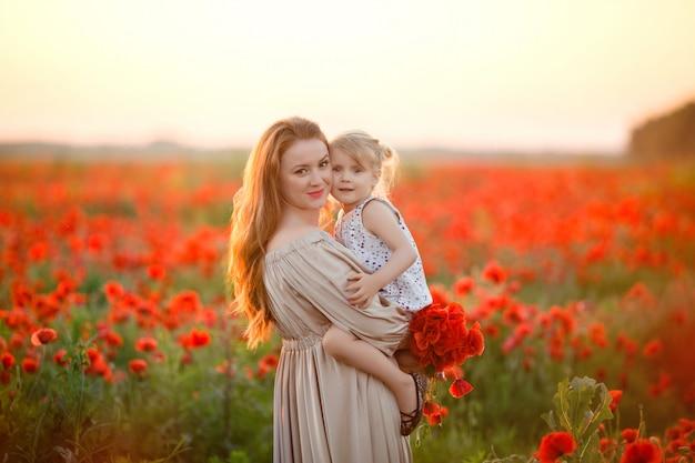 Mutter und tochter auf dem gebiet mit mohnblumen