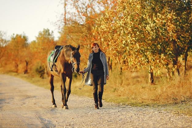 Mutter und tochter auf einem gebiet, das mit einem pferd spielt