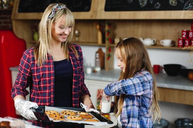 Mutter und tochter auf einer küche schmecken frisch gebackene schokoladenplätzchen mit milch