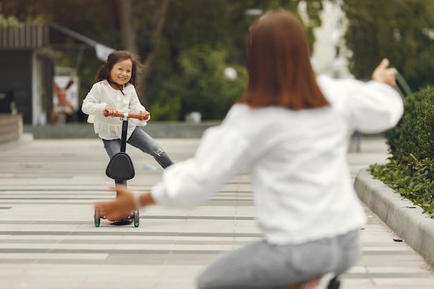 Mutter und tochter auf tretroller im park. kinder lernen rollschuh laufen. kleines mädchen, das am sonnigen sommertag schlittschuh läuft.