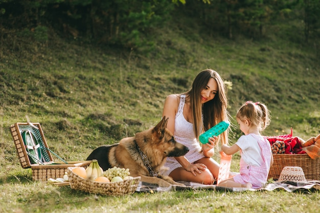 Mutter und tochter bei einem picknick mit einem hund