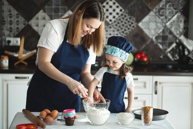 Mutter und tochter bereiten einen süßen kuchen vor