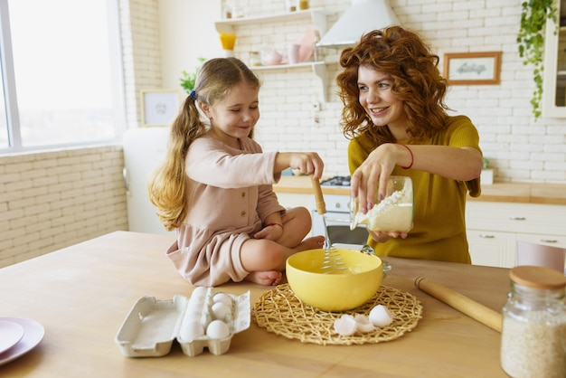 Mutter und tochter bereiten gemeinsam in der küche einen kuchen zu
