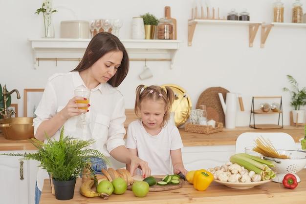 Mutter und tochter bereiten in der küche einen salat zu. glückliche liebevolle familie bereiten sich zusammen vor. das konzept einer gesunden ernährung und lebensweise. familienwert.