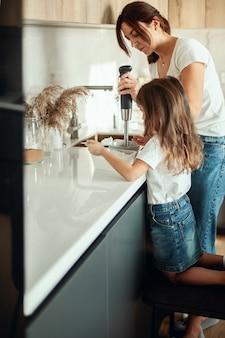 Mutter und tochter bereiten in ihrer wohnküche das sahnehäubchen für lebkuchen vor. mit einem mixer schlagen. das mädchen