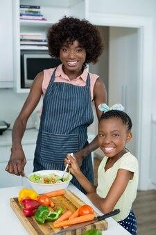 Mutter und tochter bereiten salat in der küche zu hause vor