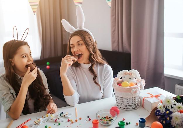 Mutter und tochter bereiten sich auf das frühstück vor. sie sitzen zusammen im zimmer und essen schokoladeneier. korb mit dekoration, farbe und süßigkeiten auf dem tisch.