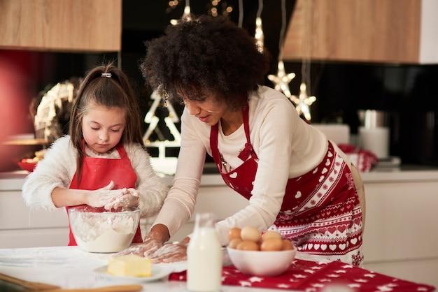 Mutter und tochter bereiten snack in der küche vor