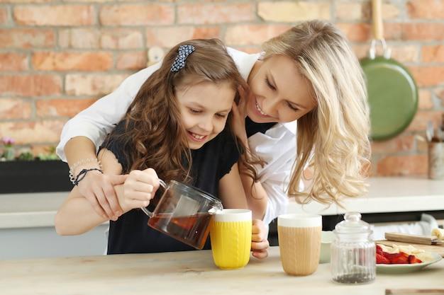 Mutter und tochter bereiten teetasse vor