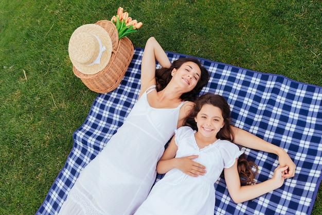 Mutter und tochter, die am picknick sich entspannen