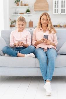 Mutter und tochter, die an den telefonen schauen