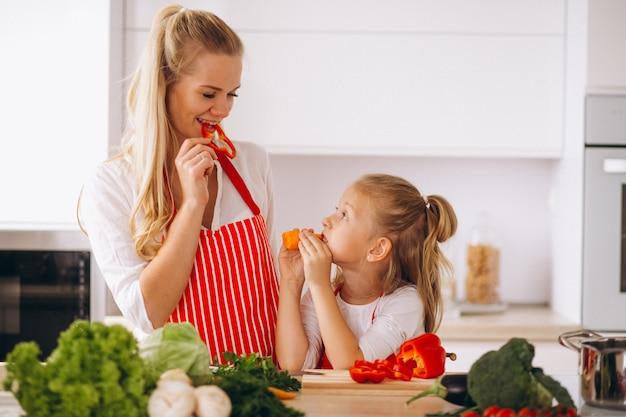Mutter und tochter, die an der küche kochen
