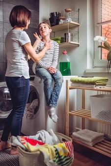 Mutter und tochter, die an der waschküche sprechen