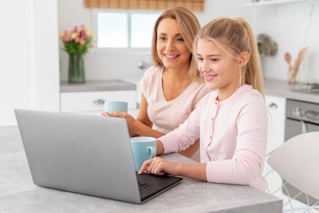 Mutter und tochter, die an laptop arbeiten