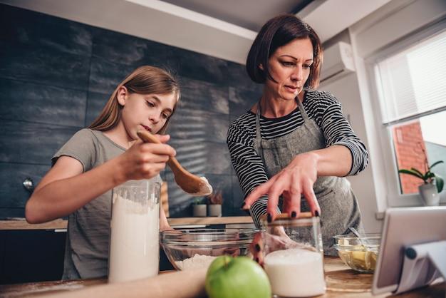 Mutter und tochter, die apfelkuchenrezept auf der tablette suchen