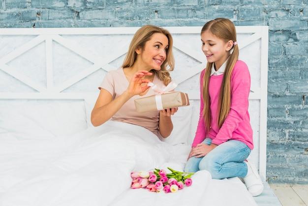 Mutter und tochter, die auf bett mit geschenkbox sitzen