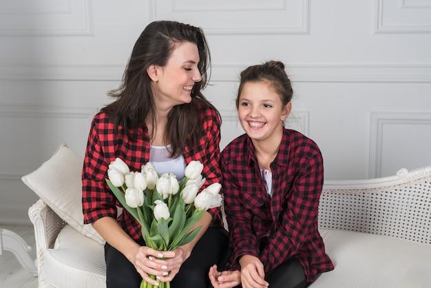 Mutter und tochter, die auf couch mit tulpen sitzen
