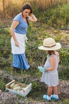 Mutter und tochter, die auf dem gebiet ernten frischgemüse stehen